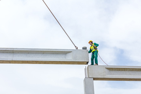rigger: Height worker is high up on concrete frame without proper safety equipment.