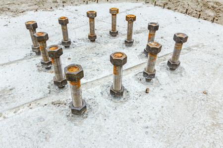 cusp: Close up the anchor bolts in concrete base of new edifice with reinforcement at building site.