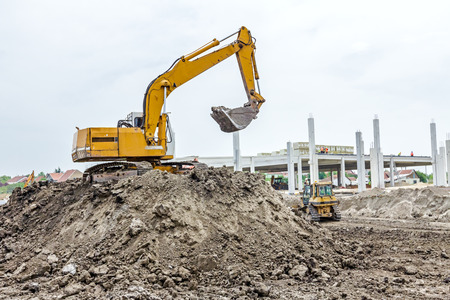 heap up: Yellow excavator is making pile of soil by pulling ground up on heap at construction site, project in progress.