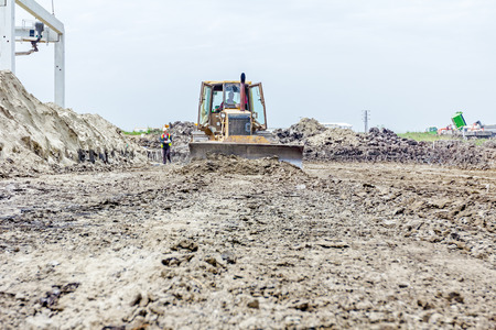 earthmover: Front view on bulldozer while he moving, leveling ground at building site.