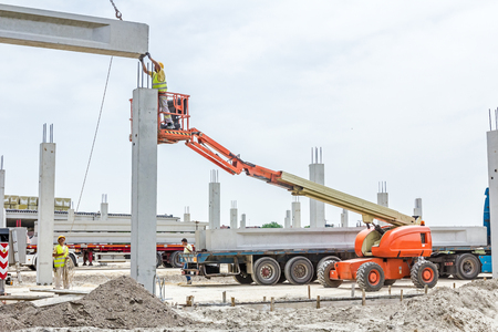 Mobile crane is operating and worker is assembly concrete joist in high place. Height worker is placing truss on building skeleton. 스톡 콘텐츠