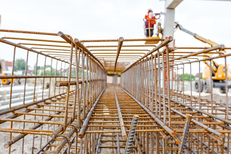 View perspective trough cage, skeleton of reinforcing steel bar at construction site. Stock Photo