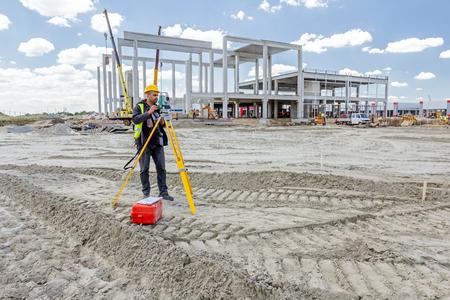 tachymeter: Zrenjanin, Vojvodina, Serbia - June 22, 2015: Surveyor engineer is measuring level on construction site. Surveyors ensure precise measurements before undertaking large construction projects.
