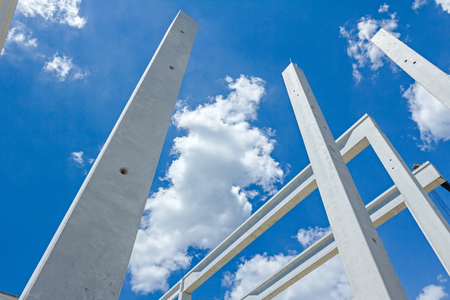Perspective view of concrete pillars, edifice in progress of growing into tall building with cloudy sky in background.