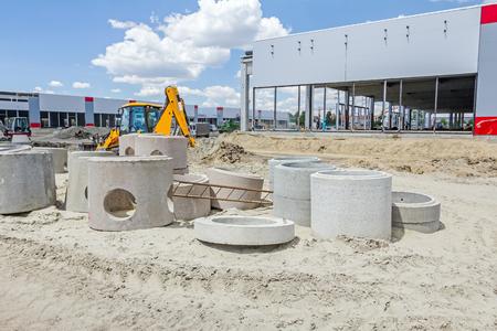 Neue Betonfertigrohre für Schacht oder Entwässerung an der Baustelle gestapelt. Standard-Bild