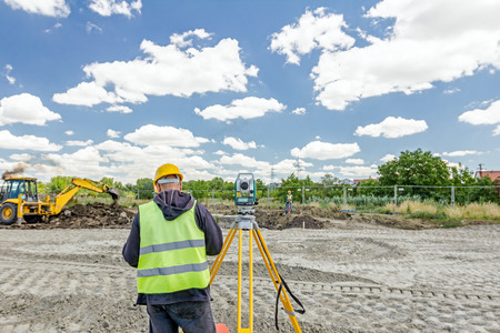 undertaking: Surveyor engineer is measuring level on construction site. Surveyors ensure precise measurements before undertaking large construction projects.
