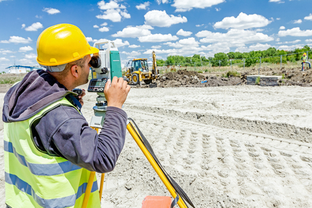 tacheometer: Zrenjanin, Vojvodina, Serbia - June 22, 2015: Surveyor engineer is measuring level on construction site. Surveyors ensure precise measurements before undertaking large construction projects.