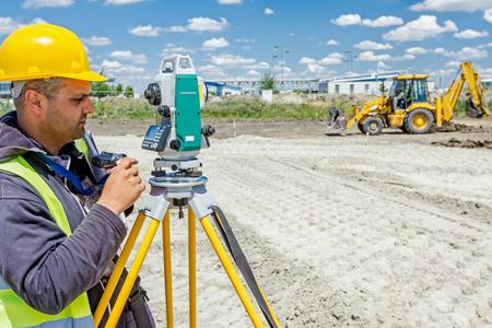 geodesist: Zrenjanin, Vojvodina, Serbia - June 22, 2015: Surveyor engineer is measuring level on construction site. Surveyors ensure precise measurements before undertaking large construction projects.