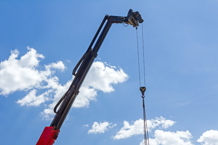 lifting hook: Telescopic mobile crane has high elevated chains for lifting hook against blue sky.