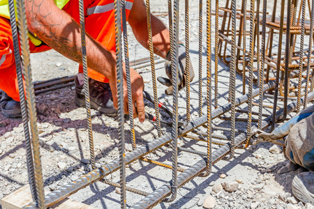 binding: Workers are tying rebar to make a newly constructed footing frame. Binding concrete frame