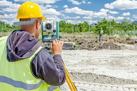 ensure: Surveyor engineer is measuring level on construction site. Surveyors ensure precise measurements before undertaking large construction projects.