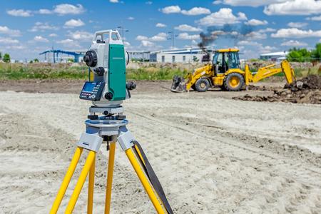Surveyor Ingenieur misst Ebene auf der Baustelle. Surveyors präzise Messungen zu gewährleisten, bevor Sie große Bauvorhaben Unternehmen.