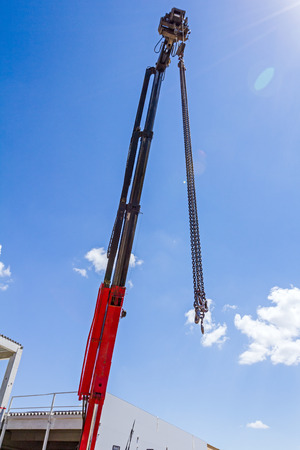 telescopic: Telescopic mobile crane has high elevated chains for lifting hook against blue sky.
