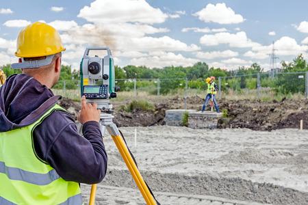 Landmeter engineer is het meten van het niveau op de bouwplaats. Landmeters zorgen voor nauwkeurige metingen voor de aanvang van grote bouwprojecten. Stockfoto - 63172531