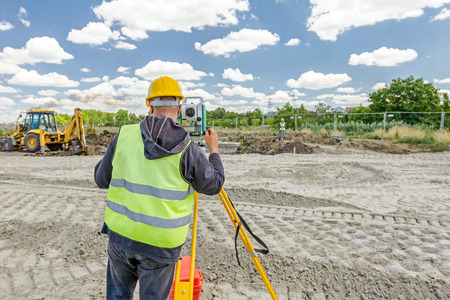 Surveyor engineer is measuring level on construction site. Surveyors ensure precise measurements before undertaking large construction projects.