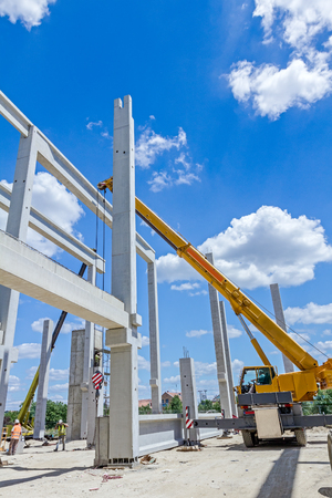 joist: Mobile crane is operating to assembly concrete joist on new edifice.