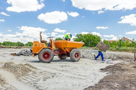 Little construction dumper carrier is at building site. Stock Photo