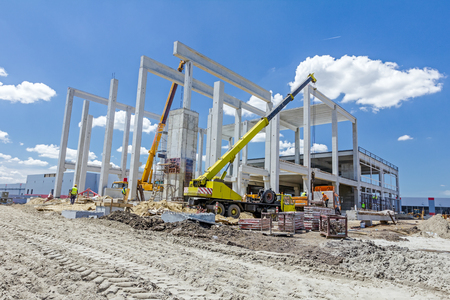 Mobile crane is working to assembly huge hall. Placing the truss on building skeleton.