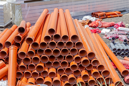 Sewer pipes waiting to be placed into the ditch at construction site. Tubes are classified according to size.