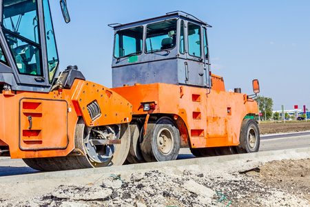 Group of machines for spreading asphalt are parked after road construction at building site. Stock Photo