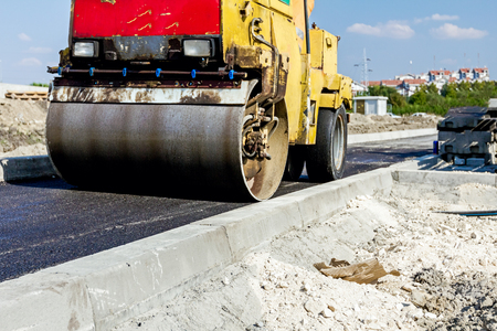curb: Small steamroller is flatting new road made of asphalt. Detail on newly installed curb. Close up view on roadside. Stock Photo