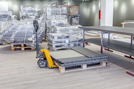 sacktruck: Yellow plastic crates, pallet jack, pedestrian stacker for transport pallets with furnishing equipment. Stock Photo