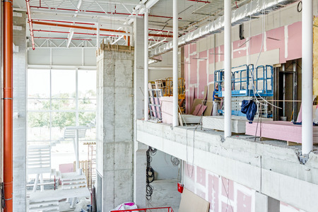 picker: Cherry picker is parked upward at indoor construction site of unfinished modern large showroom.