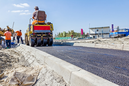 Small steamroller is flatting new road made of asphalt.