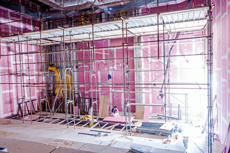 working stiff: Empty scaffolding is placed against plasterboard wall at new theater with back light from outside.