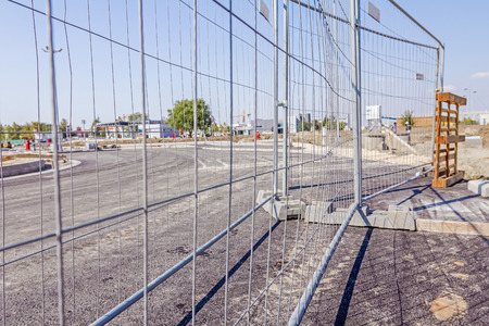 fenced in: Mobile steel fence as a barrier. Restricted area, for the authorized personnel only. Construction site has a safety rules.