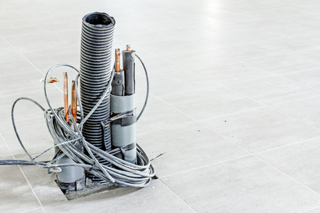 energia electrica: Manojo de varios cables eléctricos en tubo corrugado está saliendo de las baldosas del suelo, listo para ser conectado a la unidad de potencia. Foto de archivo