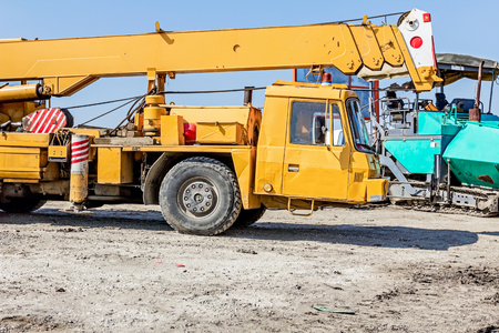 polea: Oxidada grúa móvil de edad se parquea en el sitio de construcción. Paisaje se transforma en zona urbana. Foto de archivo