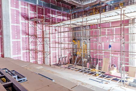 plasterboard: Empty scaffolding is placed against plasterboard wall at new theater with back light from outside.