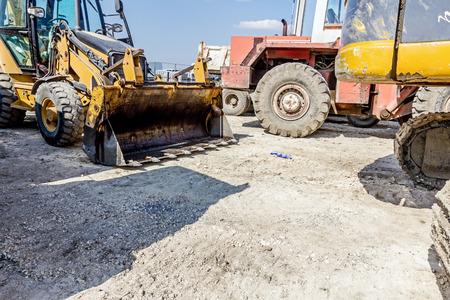 cargador frontal: Ver en el extremo delantero de la cargadora, retroexcavadora tractor estacionado en el lugar de la construcción.