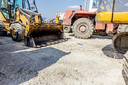 front loader: View on front end of loader, backhoe tractor parked at construction site. Stock Photo