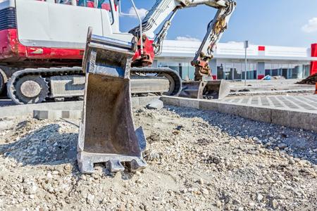 Excavadora pequeña quita el asfalto roto y grava en el sitio de construcción.