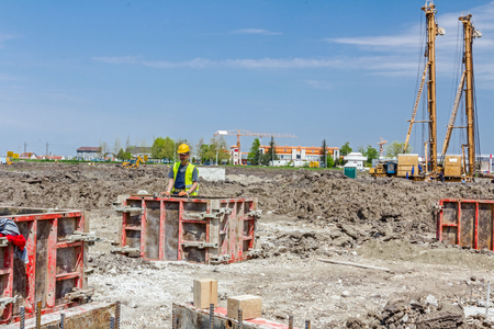 rigger: Zrenjanin, Vojvodina, Serbia - June 14, 2015: View on building site until workers are assembly demountable wooden mold for concreting pillar base. Editorial