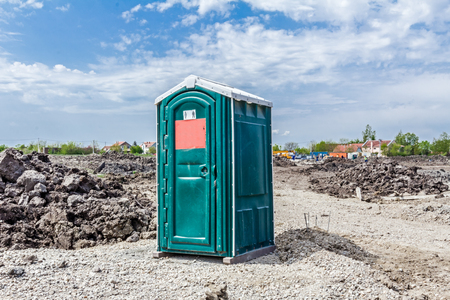 Transportable modern designed public street toilet is placed at building site, outdoor privacy. Stock Photo
