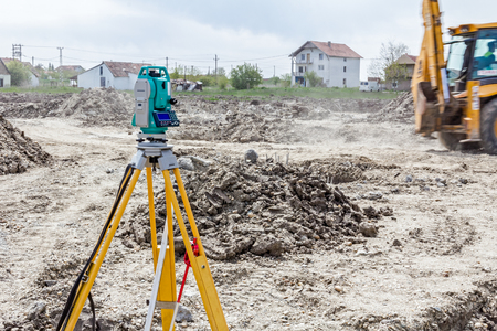 undertaking: Surveyor engineers equipment for measuring level on construction site. Surveyors ensure precise measurements before undertaking large construction projects.