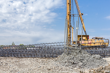 enveloped: Basic profile made of bended and tied reinforcing rod in a round shape. Pile driving machine with big auger, equipment for drilling into the ground.