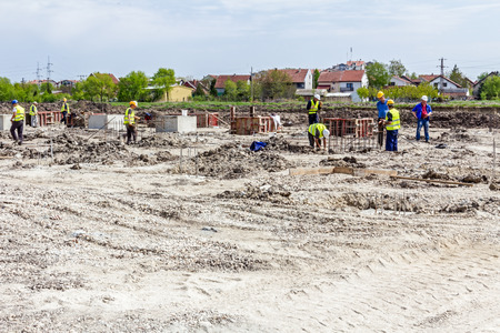 Zrenjanin, Vojvodina, Serbien - 14. Juni 2015: Auf der Baustelle bis zum Arbeiter zum Betonieren Säulenbasisbaugruppe demontierbar Holzform sind.