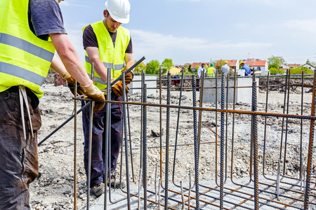 site preparation: Zrenjanin, Vojvodina, Serbia - June 14, 2015: Workers are tying rebar to make a newly constructed footing frame. Binding concrete frame