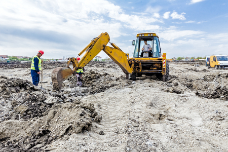 manpower: Zrenjanin, Vojvodina, Serbia - June 14, 2015: Backhoe tractor is working on a construction site. Group of workers with shovels are digging.