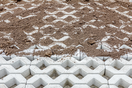 precast: Leveling and filling out symmetrical and decorative precast cobblestone shape with ground.