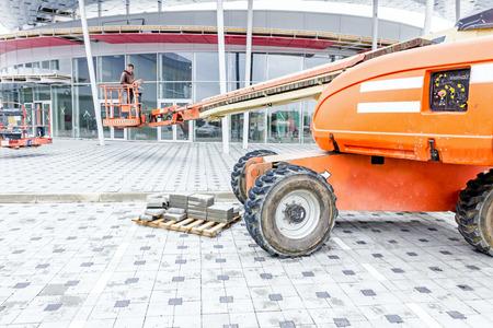 Zrenjanin, Vojvodina, Serbia - September 25, 2015: Cherry picker is moving over tiled ground at construction site.