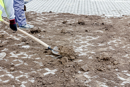earthwork: Workers are filling out symmetrical and decorative precast cobblestone shape with ground using shovel. Stock Photo