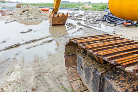 front end loader: View under the arm of excavator. Reflection on water surface, construction site after rain