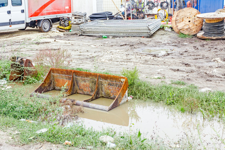 earthmover: Makeshift storage material at construction site in the improvised warehouse after rain. Stock Photo
