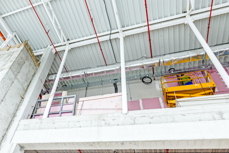 undone: Cherry picker is parked upward at indoor construction site of unfinished modern large showroom.
