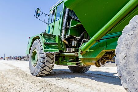 manage transportation: Big hydraulic dumper truck is moving over sandy ground at building site. Low angle view